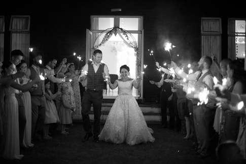 Bride and groom walking through sparkler tunnel