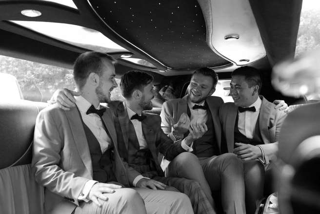 Natural photography of groomsmen in limousine