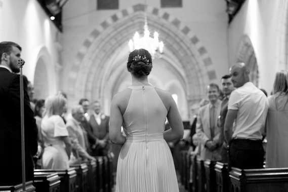 Bridesmaid walking down aisle at church