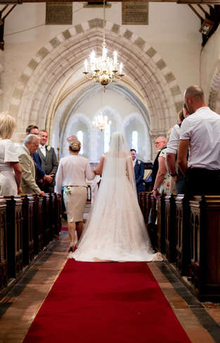 Photo of Mother giving daughter away at church wedding ceremony