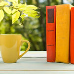 stack-of-colorful-books-and-cup-on-woode