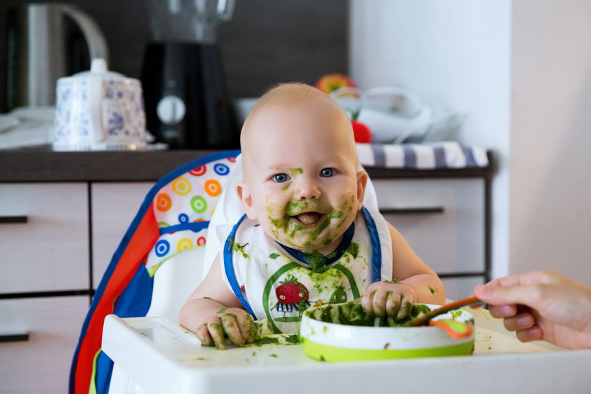 baby creating a mess while eating in a high chair, keeping a high chair clean