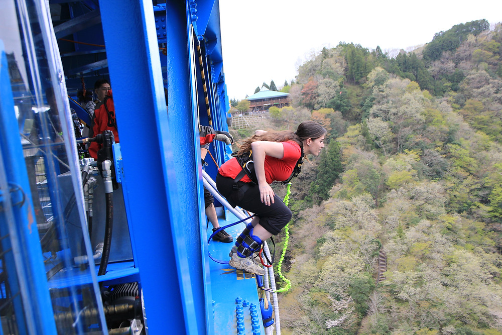 girl is braced and about to bungee jump off of a blue suspension bridge over brown hills