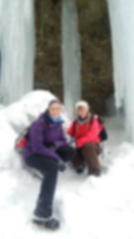 Two girls sitting on snow in front of frozen waterfalls.