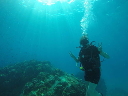 Woman scuba diving in a reef with light above.