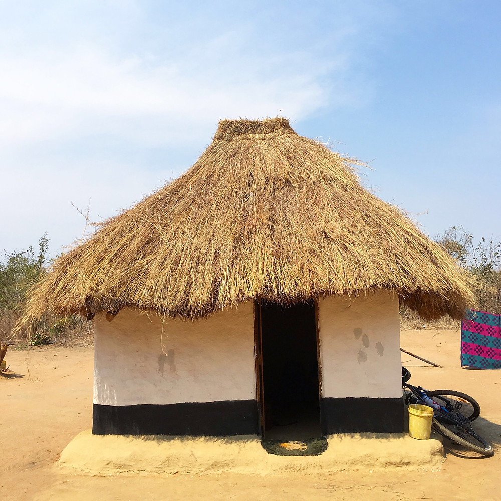 thatched roof square hut with whitewashed walls and a bike leaning against the side