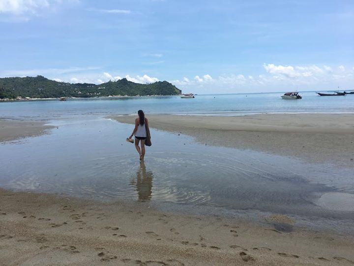 girl walking barefoot in low tide on a beach in Thailand