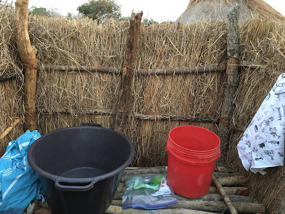 a few buckets on a wood post shelf in a grass wall area for a shower