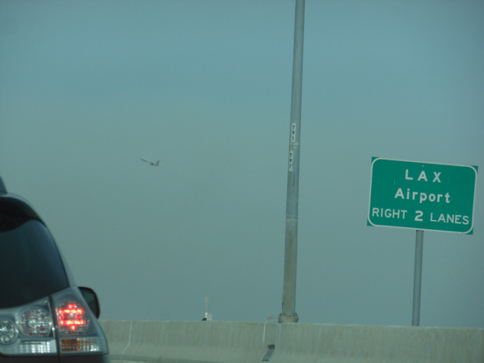 road sign for LAX airport on the freeway