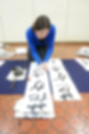 Girl doing Japanese calligrapy on the floor.