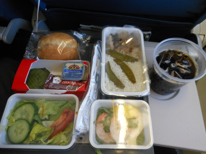 different plastic wrapped foods on a seatback tray on a plane with a soda