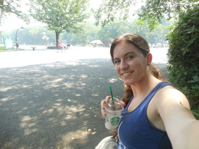 girl taking selfie with iced coffee in park