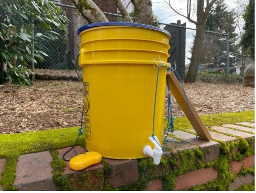 A yelllow bucket with a spout inserted illustrates the DIY hand-washing station.