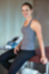 Physiotherapy, healthy fit woman sitting on chiropractic table smiling waiting to be adjusted