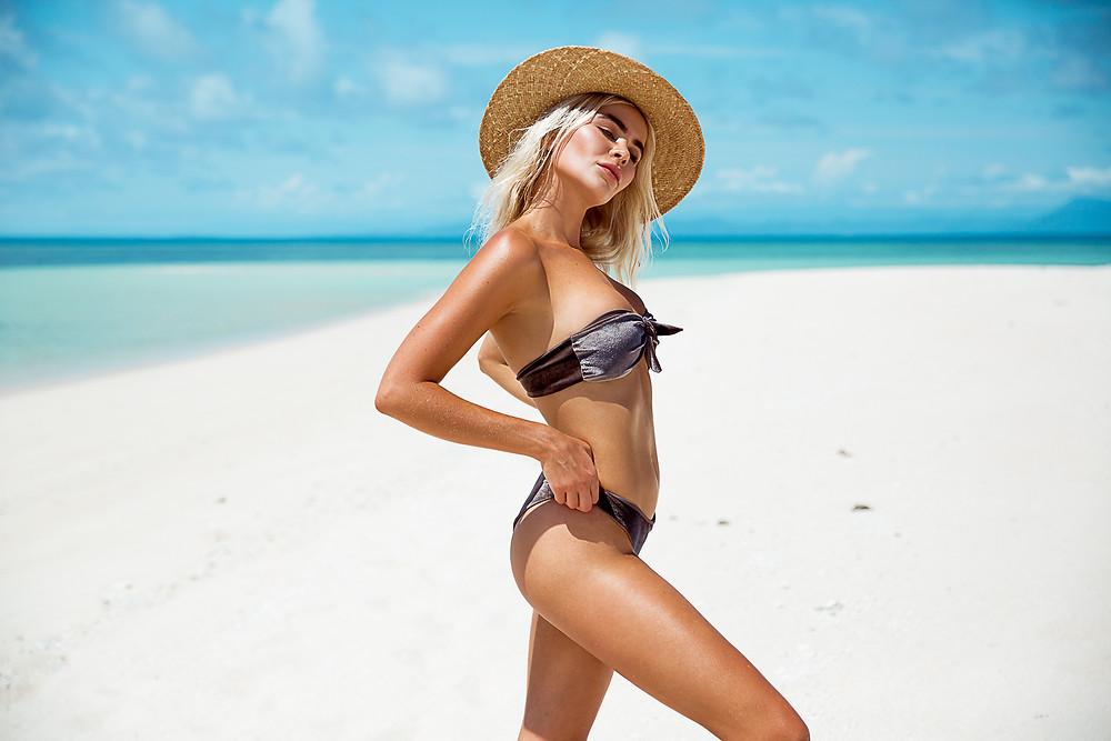 grey bikini and straw hat on beach