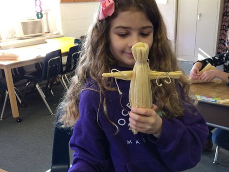 Second graders making corn husk dolls