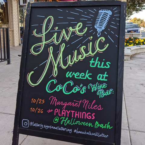 A-frame chalkboard art with weekly music acts