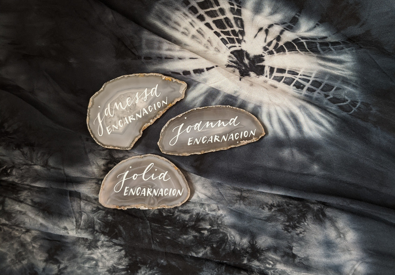 Pointed pen calligraphy on grey agate slices