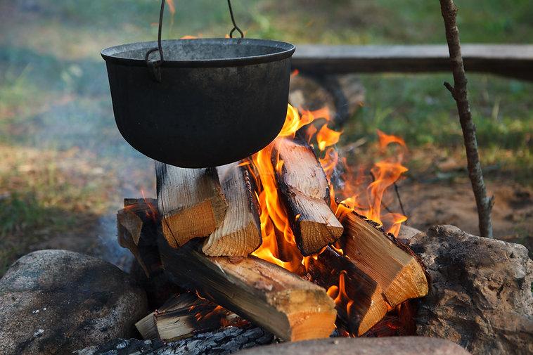 Preparing food on campfire in wild campi