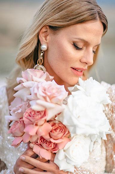 bride-holding-rose-bouquet-near-face.jpg