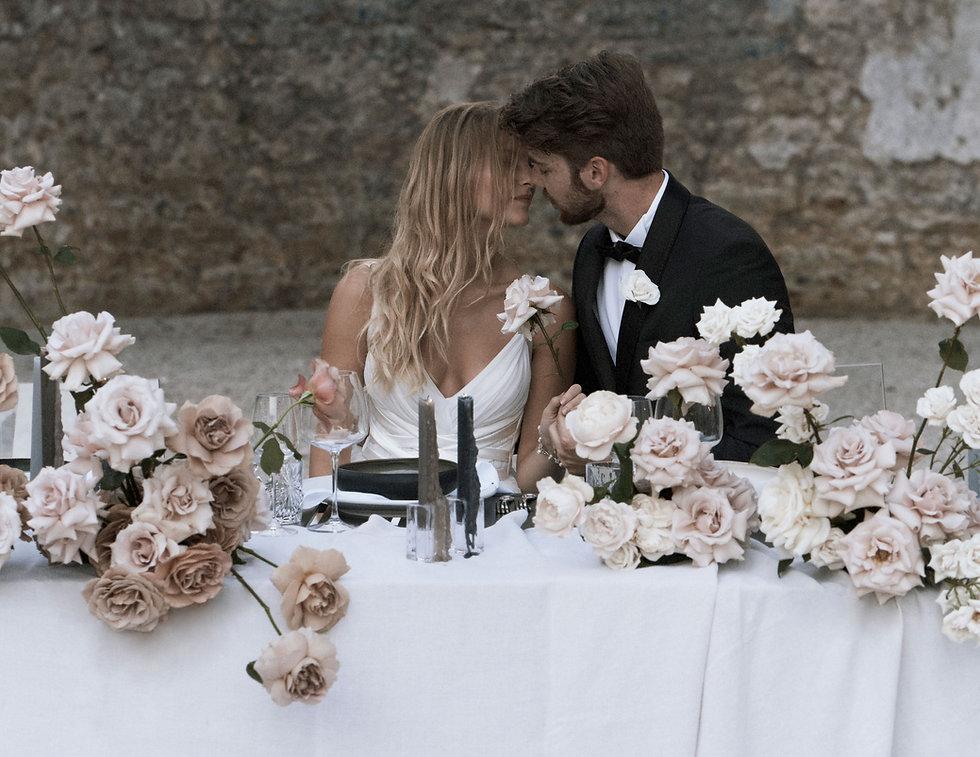 bride-groom-kissing-at-table.jpg