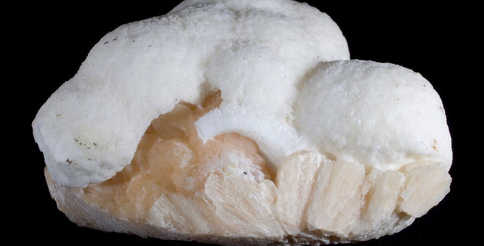 A secondary mineralization of Mordenite forms an undulating white cap, contrasting its matrix of peach Stilbite