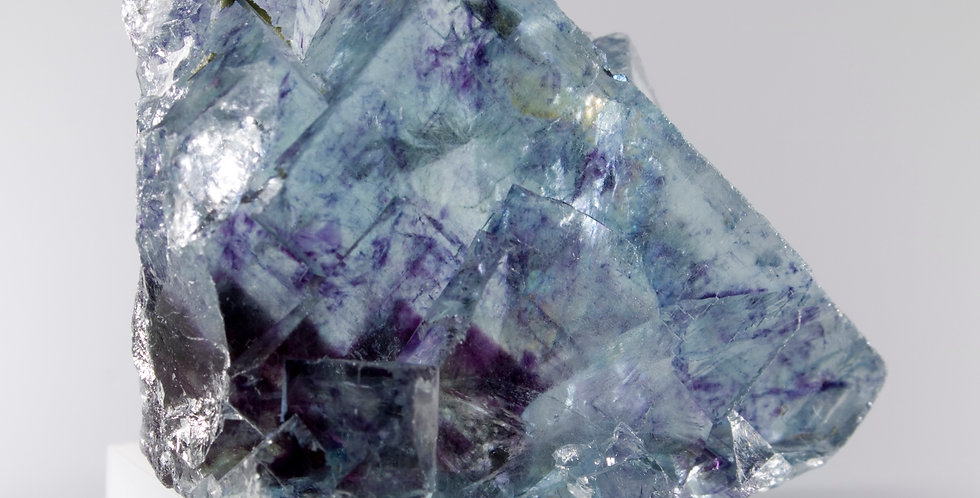 A beautiful, freestanding crystal of Clear Blue Phantom Fluorite exhibiting color zones and a heart of deep purple