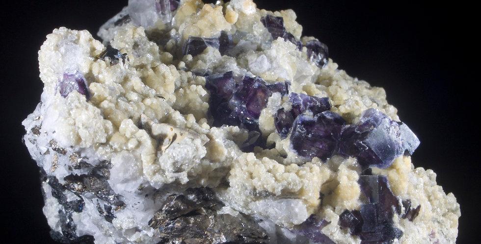A Ridge of Zoned Purple Fluorite with Pyrite & Quartz visually pops off the contrasting matrix