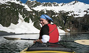 A woman in a kayak looks at the camera over her shoulder. Snowy, rocky mountains are in the background.