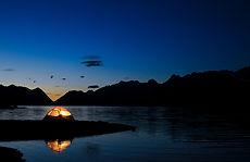 Tienda de campaña en lago de montaña nocturno