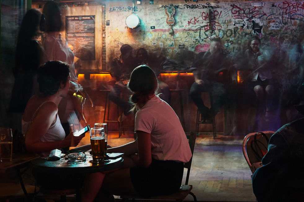 Two women in bar watching dancefloor in