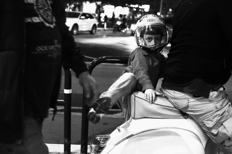 Street photo of a child getting on a bik