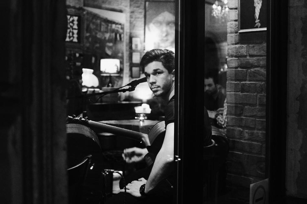 Street photo of a guitarist in a bar in