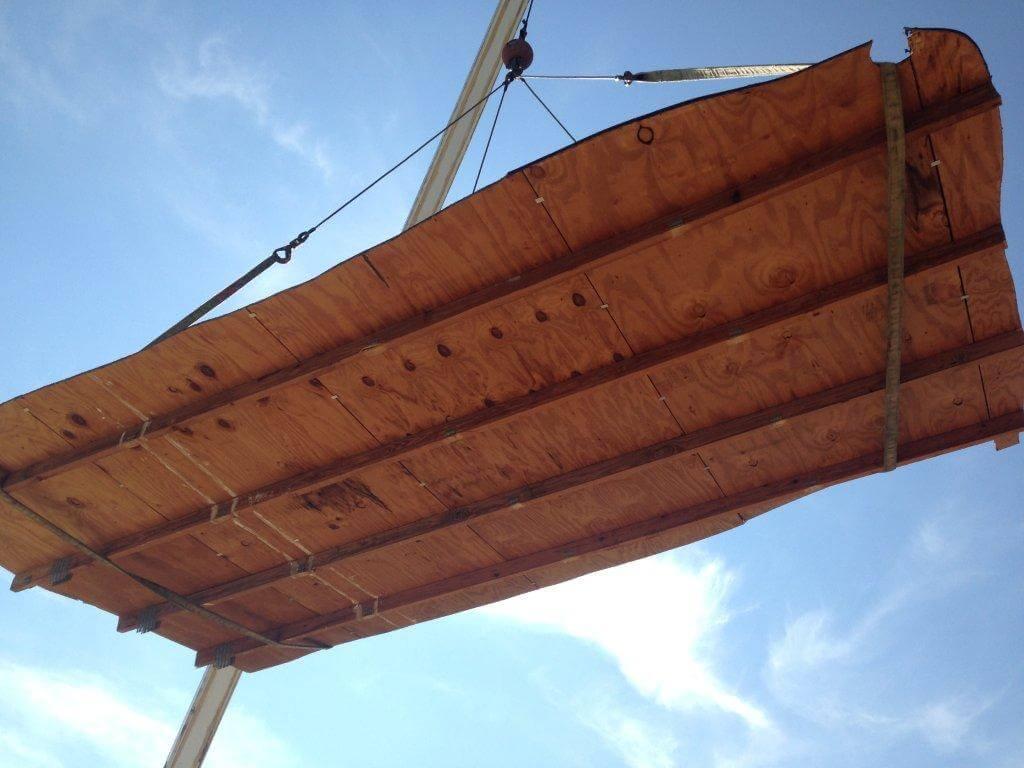 Crane holds wooden platform over