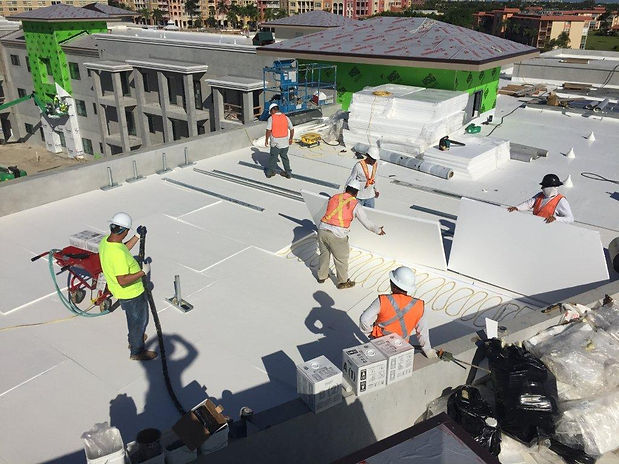 Roofing contractors laying down panels on flat roof