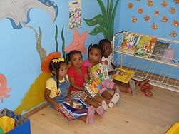 Four little girls sitting with their books