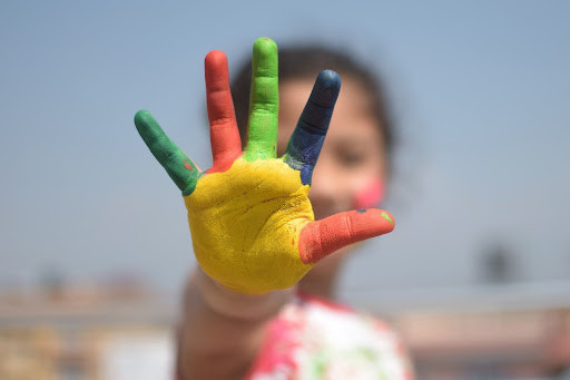 Kids hand in focus, rest of image blurred, palm is painted yellow, pinkiy green, ring finger red, middle green, index blue, and thumb red