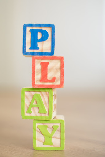 Wooden blocks stacked on top of each other spelling the word 'play'