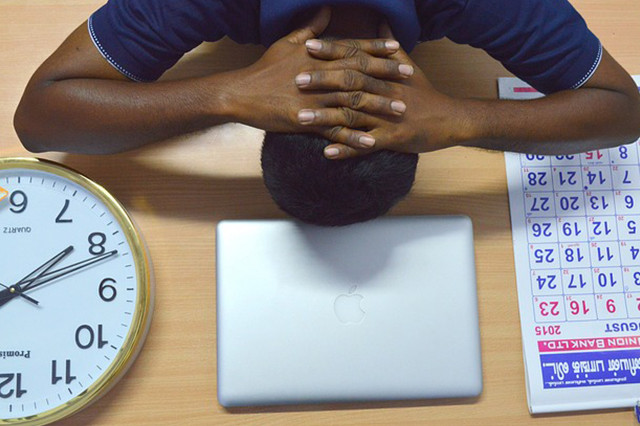 Man head down on desk stressed out over deadlines with clock and calendar on desk near laptop