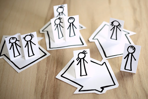 paper cut outs of people and houses with person cut outs on each house