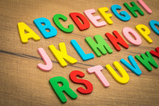 Colorful foam alphabet letters on a wooden surface