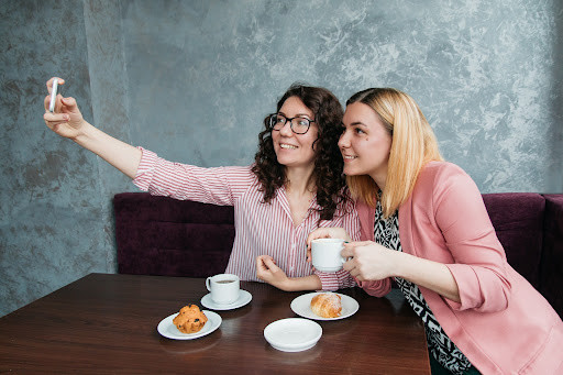 two girls taking a selfie with coffee and muffins in their booth