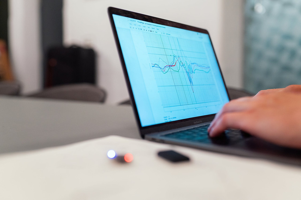 A laptop screen displaying a fluctuating graph.
