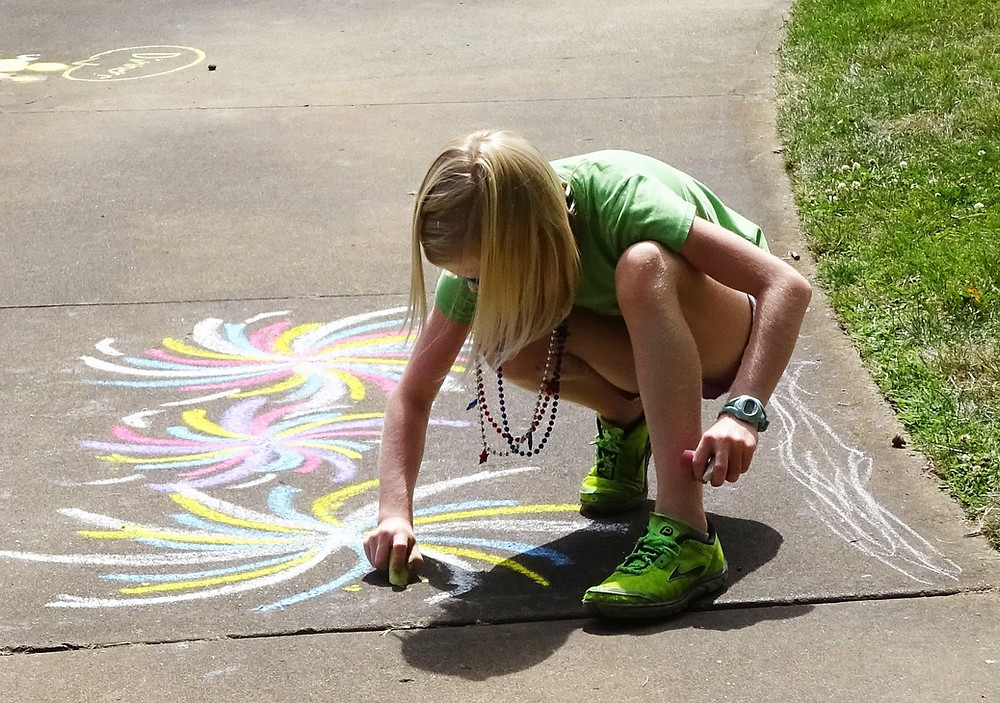 Young girl writing on sidewalk with chalk
