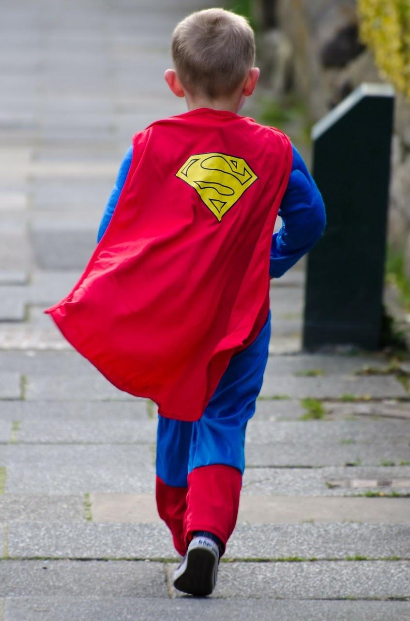 Child in a superman costume walking down the sidewalk