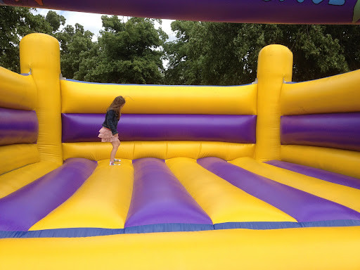 A girl jumping in a purple and yellow bounce house