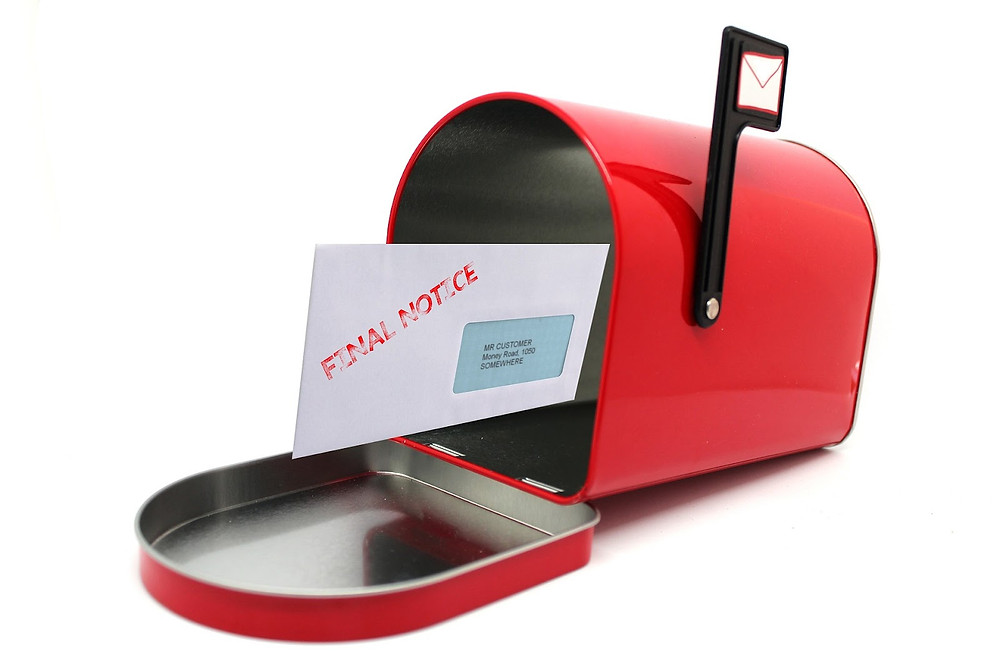 A piece of mail in a red mailbox with the flag up that states FINAL NOTICE