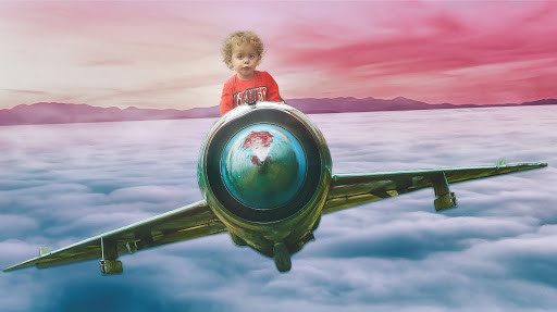 Child on airplane in the clouds