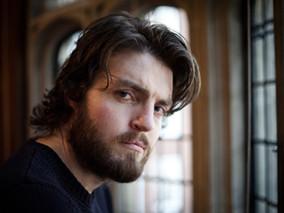 Tom Burke Cast as Cormoran Strike in Major BBC Event Drama Adaptations of The Galbriath Novels