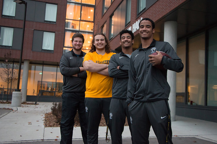 Waterloo football players in front of SJU residence